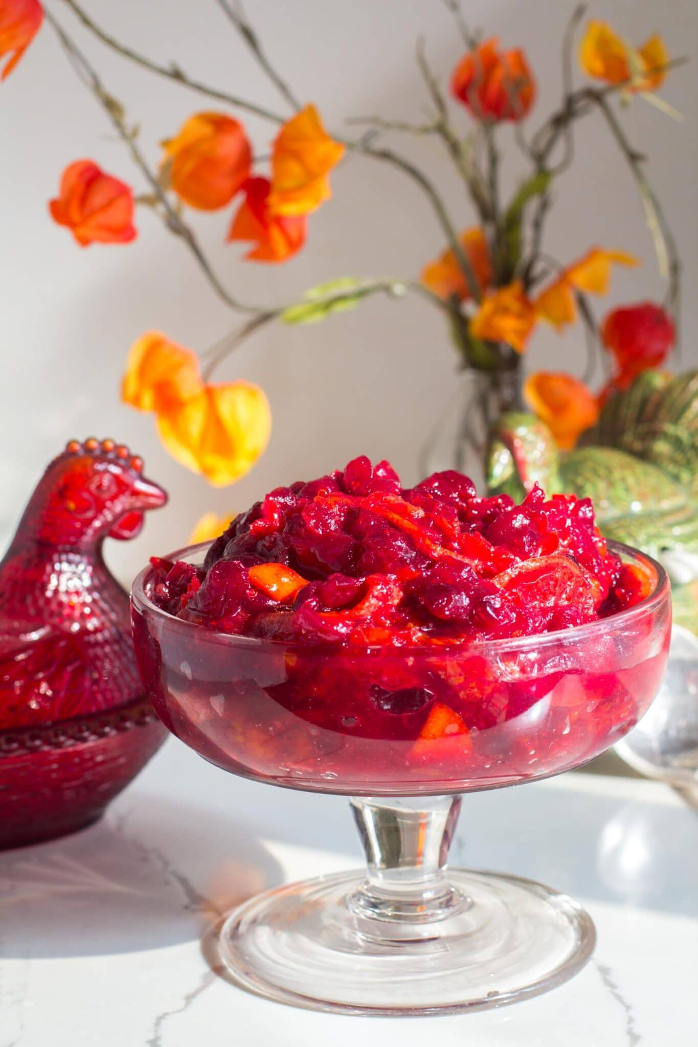 vertical image of cranberry sauce in footed glass bowl
