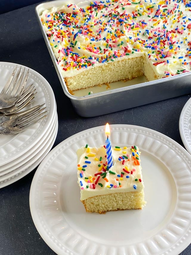 yellow-cake-with-vanilla-frosting-and-rainbow-sprinkles-on-white-plate-with-birthday-candle
