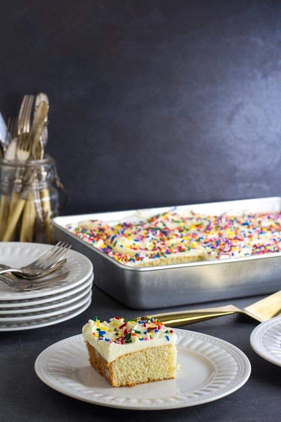yellow snack cake, in pan and on white plate, with white frosting and rainbow sprinkles
