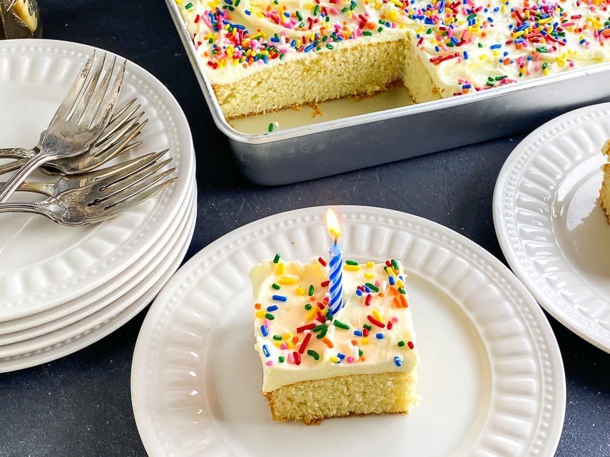 yellow snack cake with buttercream, rainbow sprinkles and blue candle on white plate