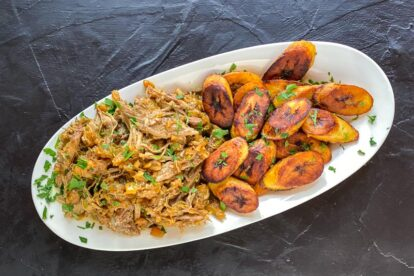 Low-FODMAP-Instant-Pot-Carribbean-Style-Pork-on-oval-whitev-plate-with-fried-plantains-dark-background