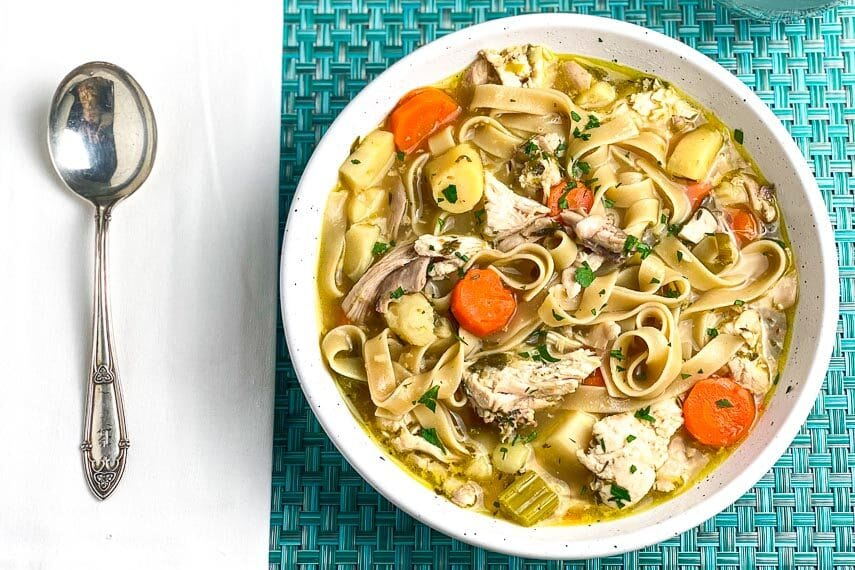 Low-FODMAP-Instant-Pot-Chicken-Noodle-Soup-with-Dill-in-white-bowl-on-aqua-placemat-and-silver-soup-spoon-white-napkin