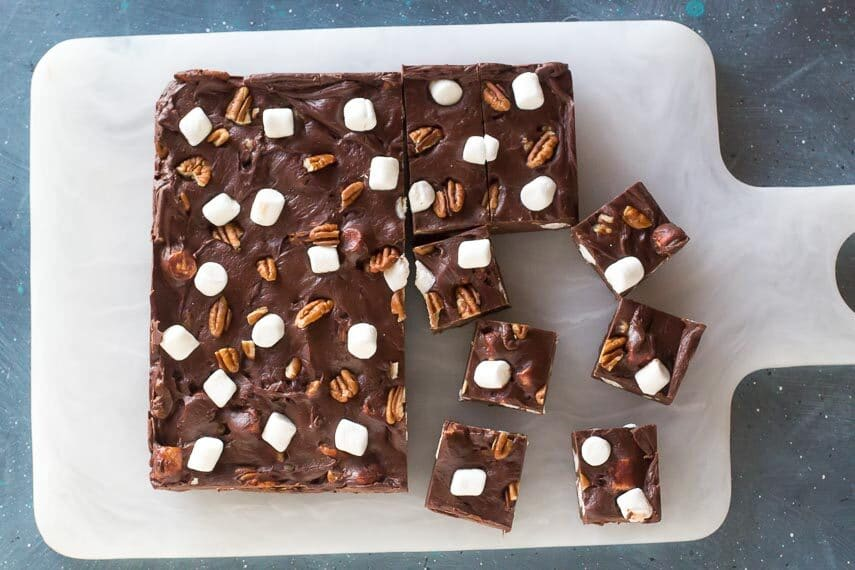 Low-FODMAP-Rocky-Road-Fudge-cut-into-squares-on-white-board-against-blue-background