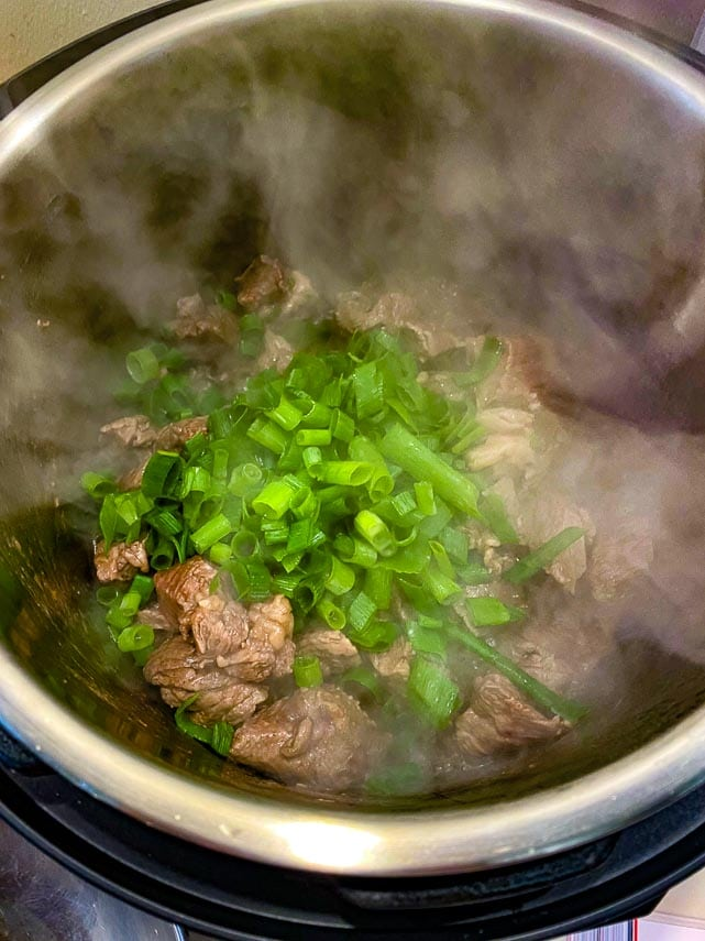 adding-chopped-scallion-greens-to-beef-cubes-in-Instant-Pot