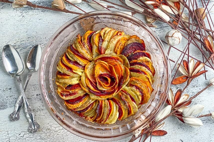 baked-root-vegetable-tian-in-glass-dish-on-white-painted-surface