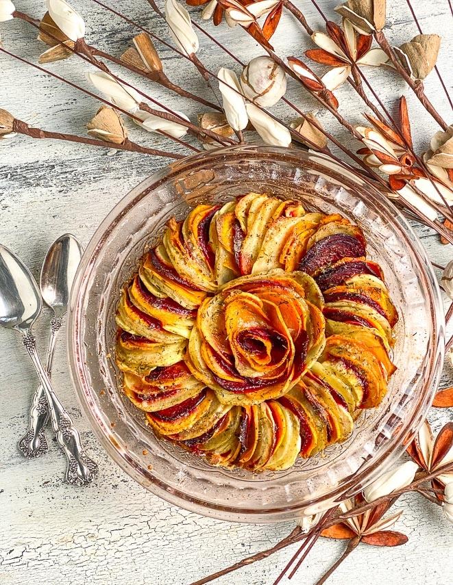 baked-root-vegetable-tian-in-glass-dish-on-white-painted-surface-ready-to-eat