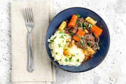 horizontal-overhead-image-of-Low-FODMAP-Instant-Pot-Beef-Stew-in-blue-bowl-on-gray-background