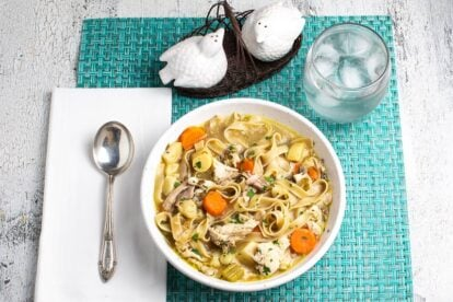 low-FODMAP-Instant-Pot-Chicken-Noodle-Soup-in-a-white-bowl-on-an-aqua-placemat-with-a-water-glass