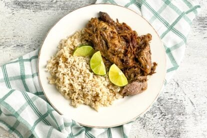 plated-low-FODMAP-Instant-Pot-Cuban-Style-Pork-on-white-plate-with-brown-rice-and-limes-white-painted-wood-background