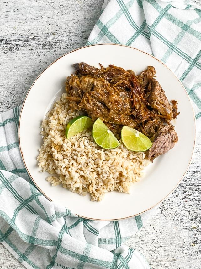 plated-low-FODMAP-Instant-Pot-Cuban-Style-Pork-on-white-plate-with-brown-rice-and-limes-white-painted-wood-background-vertical-image
