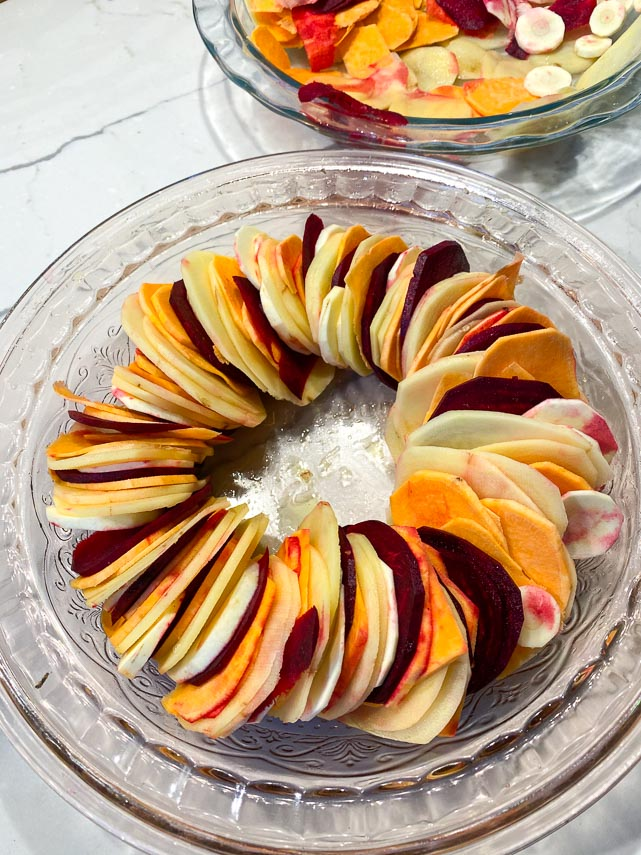 sliced-root-vegetables-layererd-in-a-glass-dish-creating-a-ring