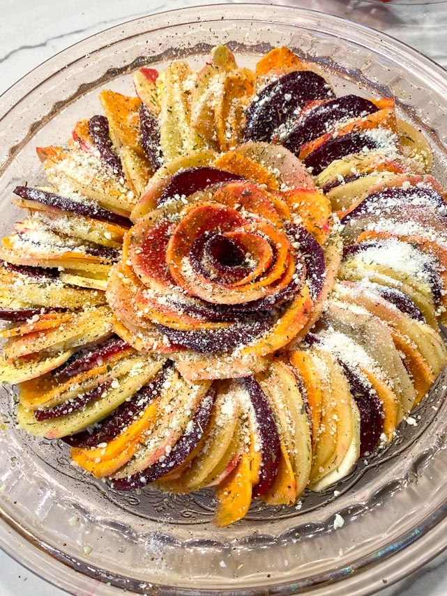 sliced-root-vegetables-layererd-in-a-glass-dish-sprinkled-with-Parmesan-cheese-and-dried-thyme