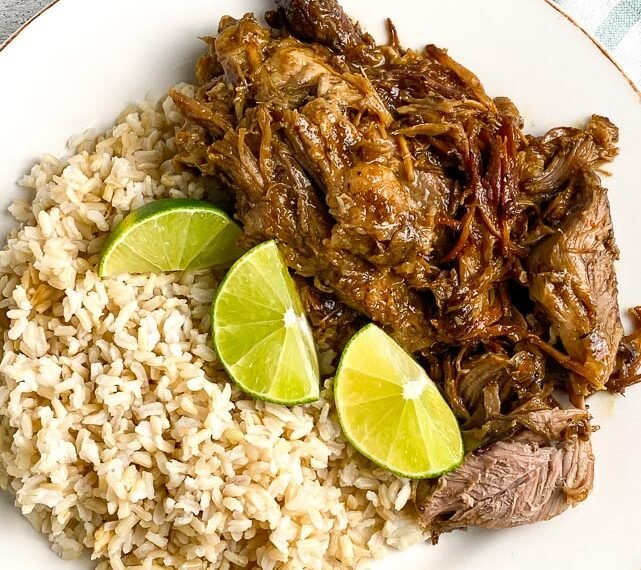 vertical-image-plated-low-FODMAP-Instant-Pot-Cuban-Style-Pork-on-white-plate-with-brown-rice-and-limes-white-painted-wood-background