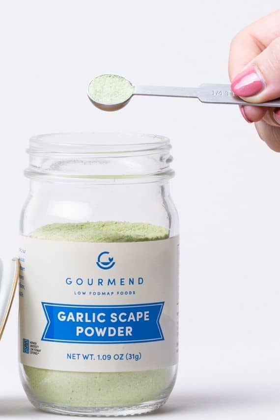 A jar of garlic scape powder viewed from the side with a hand scooping some with a spoon