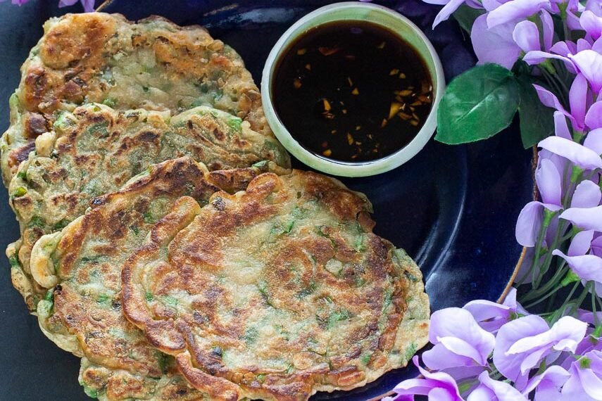 Low-FODMAP-scallion-pancakes-on-dark-plate-with-dark-background-with-dipping-sauce-and-purple-flowers-2AP
