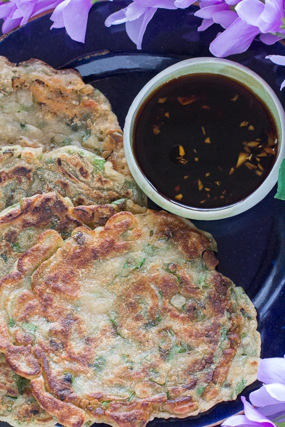 Low-FODMAP-scallion-pancakes-on-dark-plate-with-dark-background-with-dipping-sauce-and-purple-flowers-closeup