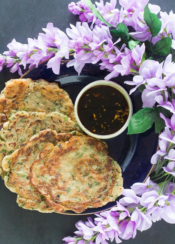Low-FODMAP-scallion-pancakes-on-dark-plate-with-dark-background-with-dipping-sauce-and-purple-flowers