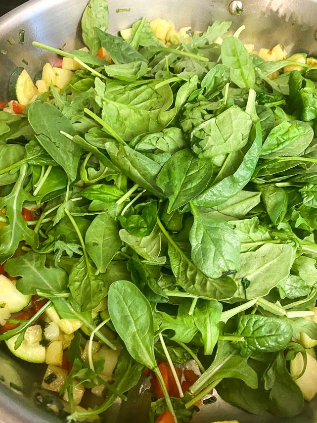 adding-baby-greens-to-pan-holding-sauteed-vegetables-for-frittata