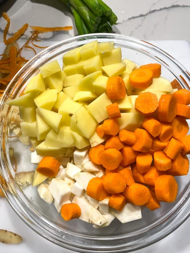 chopped-peeled-carrots-potatoes-and-celery-root-in-glass-bowl