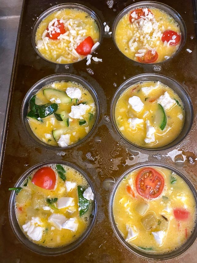 raw-frittata-mixture-in-muffin-cups-ready-to-be-baked-feta-and-cheeses-on-top