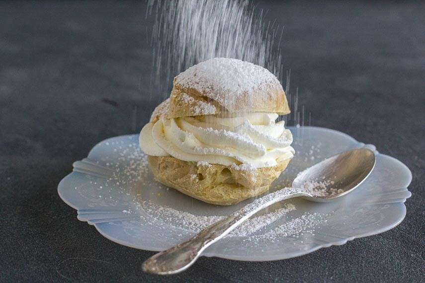 showering a cream puff with confectioners' sugar