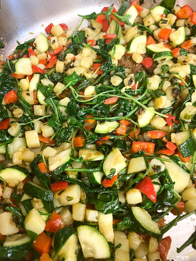 wilted-greens-and-sauteed-vegetables-in-pan-on-stove