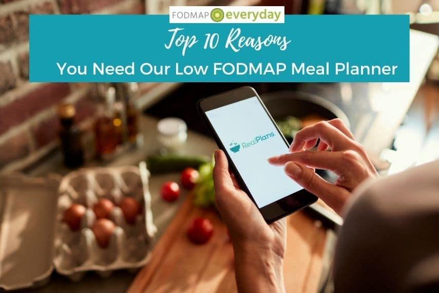 Top 10 Reasons you need our low fodmap meal planner. Image of woman holding her cell phone looking at her meal planner with kitchen counter and ingredients laid out below her hand.