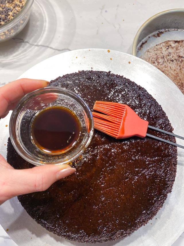 applying-low-FODMAP-coffee-liqueur-to-chocolate-cake-on-cake-decorating-turntable