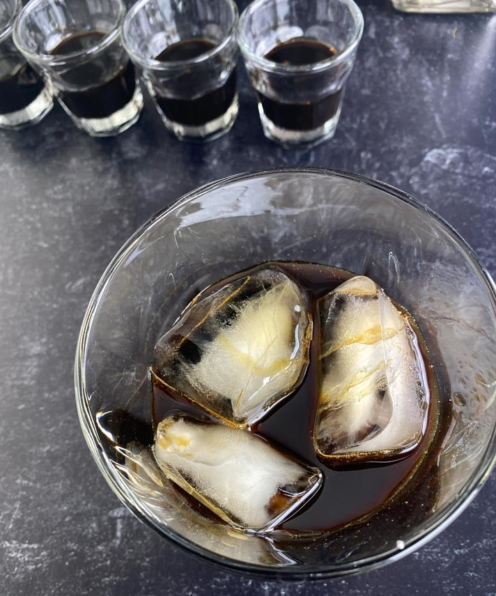 low-FODMAP-coffee-liqueur-shot-overhead-looking-down-into-glass-filled-with-ice-on-dark-table