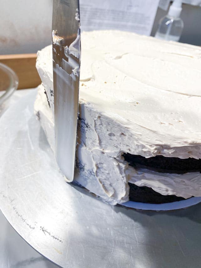 using-carboard-round-to-guide-icing-spatula-when-applying-buttercream