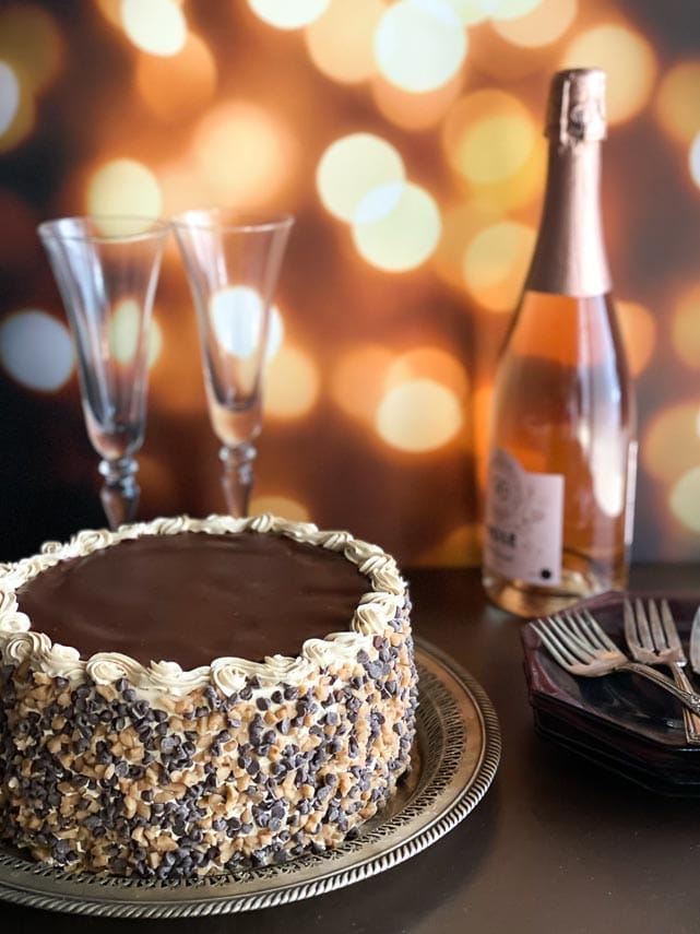 vertical-image-of-low-FODMAP-Mocha-Toffee-Crunch-Cake-on-dark-surface-champagne-bottle-and-glasses-in-background