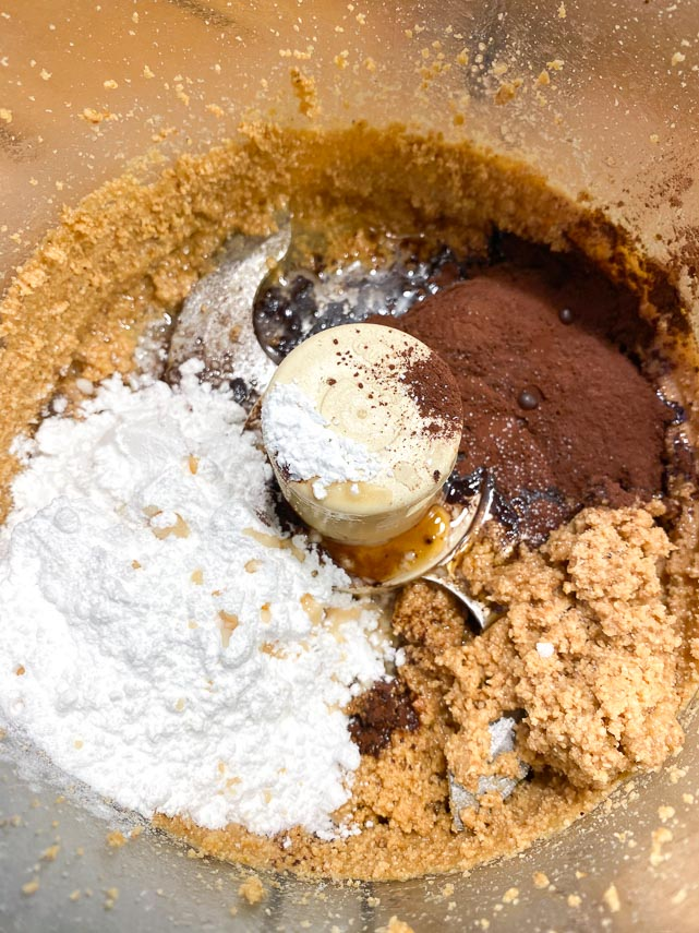 Adding confectioners' sugar, cocoa, vanilla and salt to food processor holding ground hazelnuts for making homemade low FODMAP Nutella