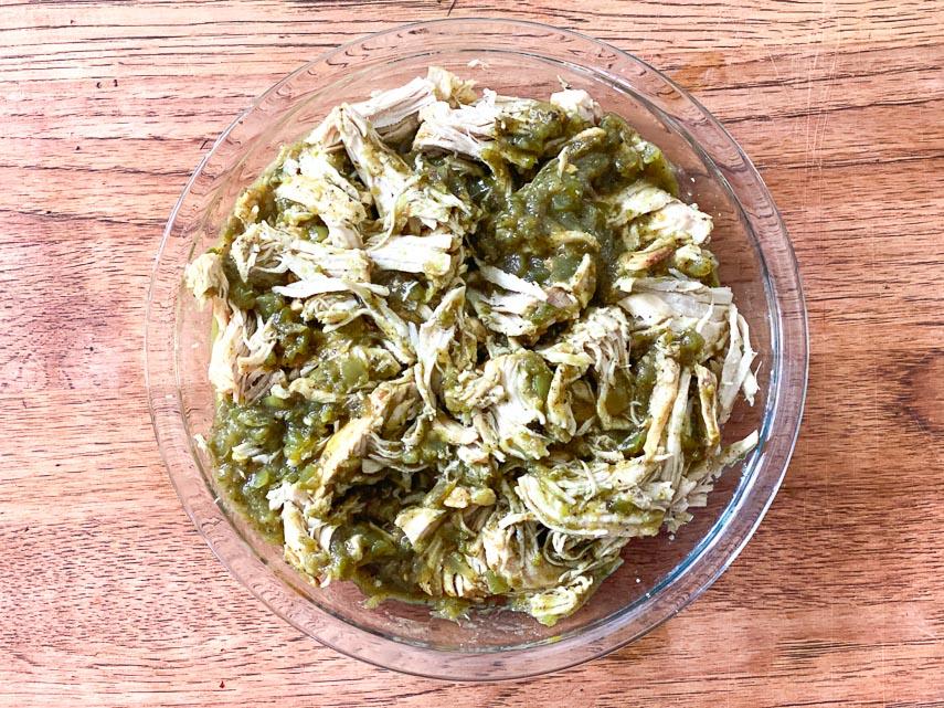 Instant-Pot-Salsa-Verde-Chicken-in-glass-bowl-on-wooden-board-1