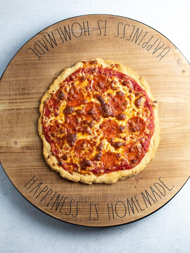 Low FODMAP Easy Pizza with Pepperoni on round wooden board