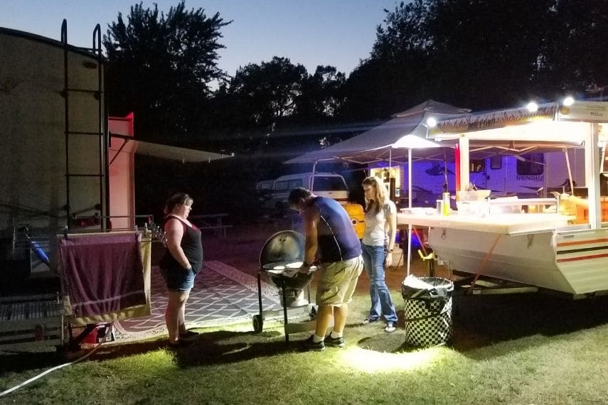 Night shot of three people at a camp sight standing around a bbq grill.