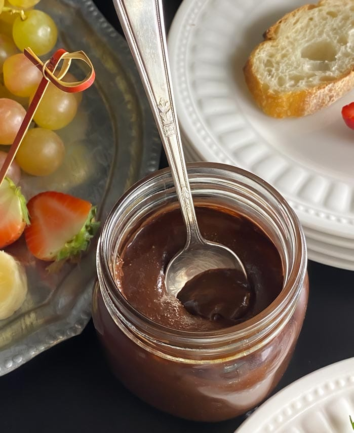 closeup of homemade Nutella in glass jar with spoon