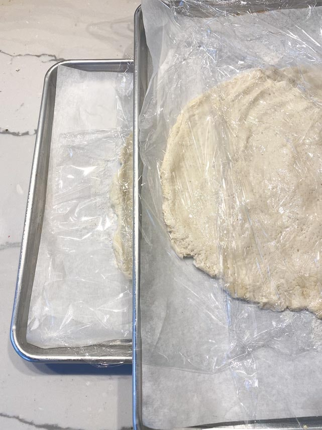 easy low FODMAP pizza dough patted out on sheetpans for rising, covered with plastic