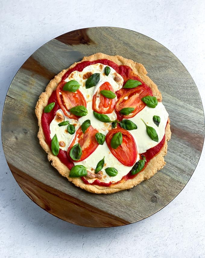 easy pizza with fresh mozarella, fresh tomatoes and fresh basil on round wooden platter
