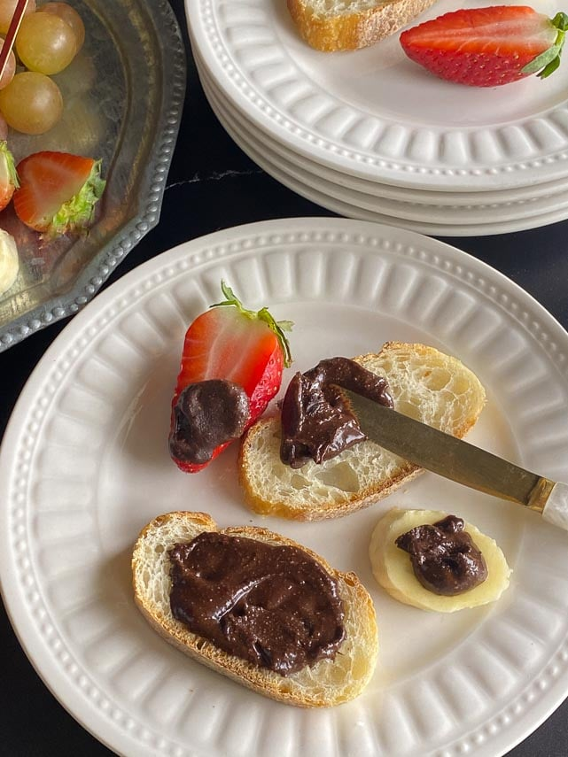 homemade Nutella on bread, strawberries and banana on white plate