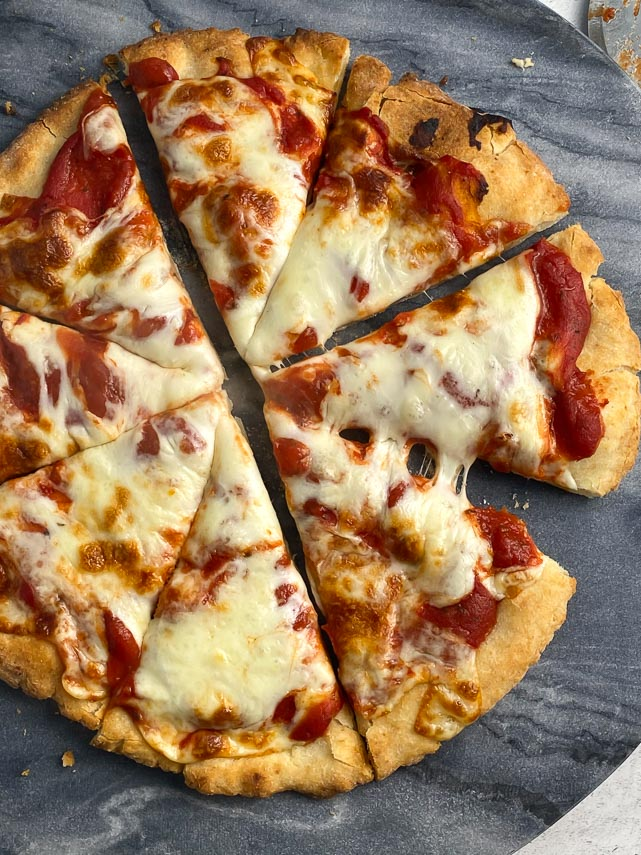 low FODMAP Pizza 2.0 on marble round, cut into wedges with gooey cheese