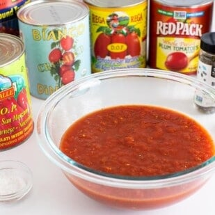 low FODMAP Pizza Sauce in glass bowl with cans of tomato products on white background