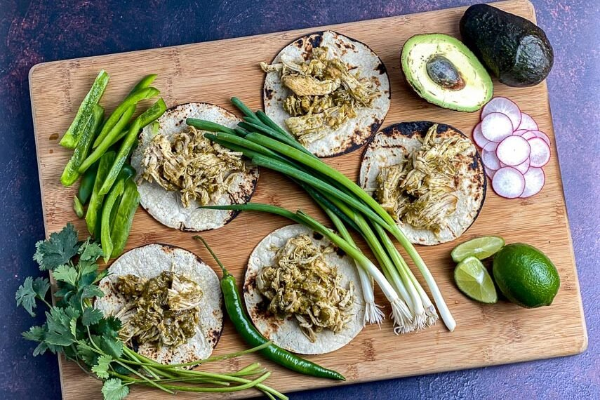 overhead-view-of-Instant-Pot-Salsa-Verde-Chicken-on-corn-tortillas-on-a-wooden-board-with-scallions-avocado-hot-chile-green-peppers-radish-and-limes-1