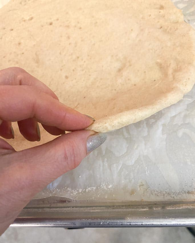 par-baking pizza crust on pan, testing with fingers for doneness