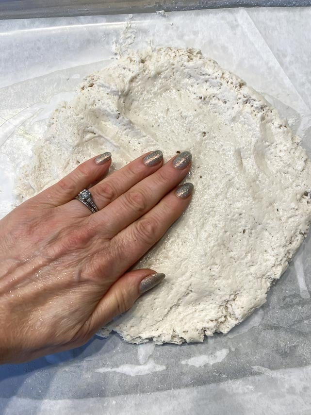 patting out pizza dough on pan