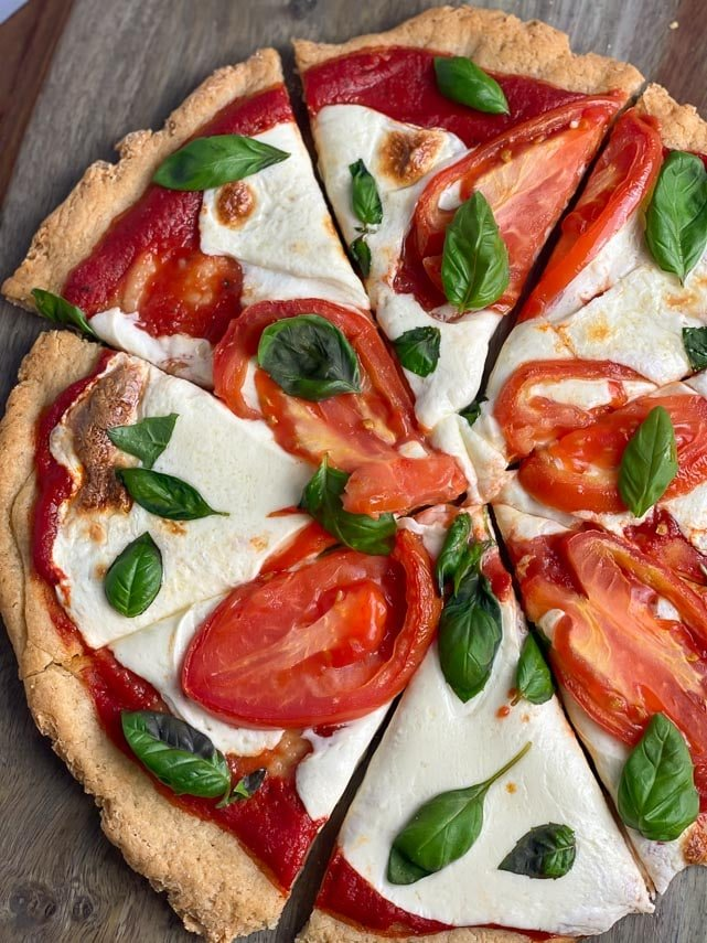 pizza with fresh mozzarella, tomatoes and basil, cut into wedges, on wooden board