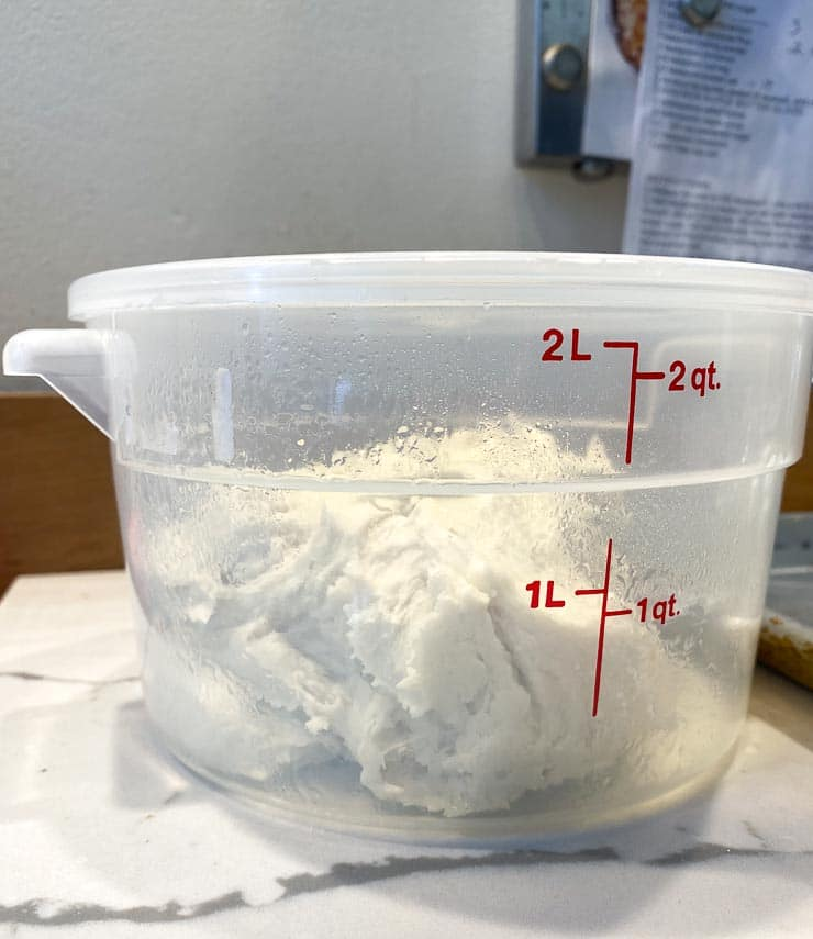 scrape pizza dough into plastic container, top snapped on top