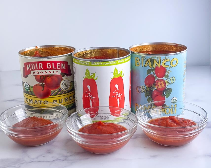tomato products lined up and compared, in cans and in bowls