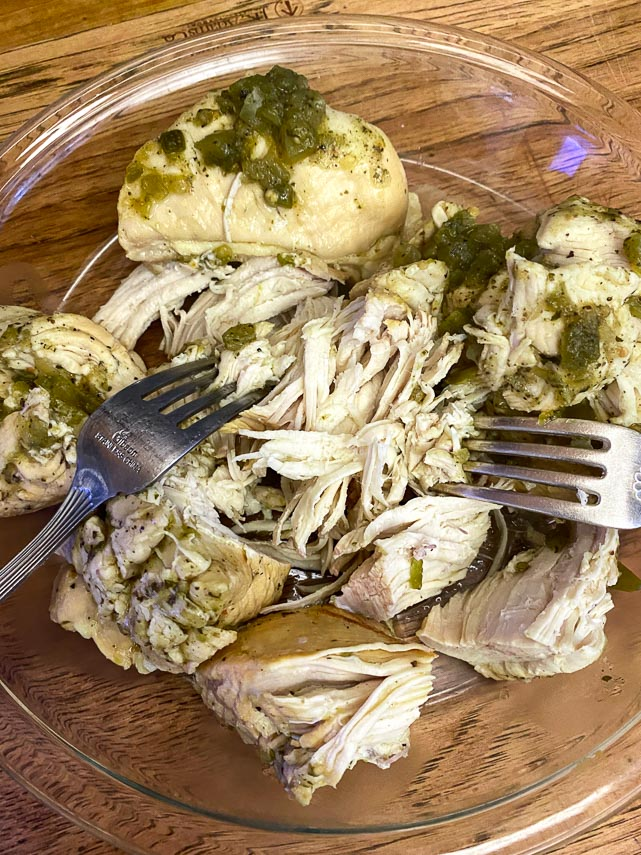 using-two-forks-to-shred-chicken-in-glass-bowl
