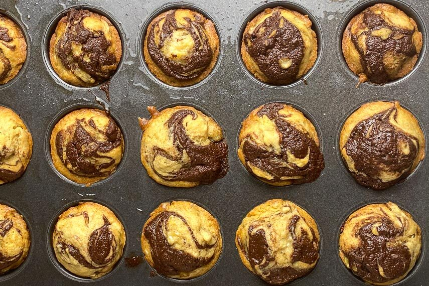 Baked mini Nutella Banana Muffins in tin, just out of oven