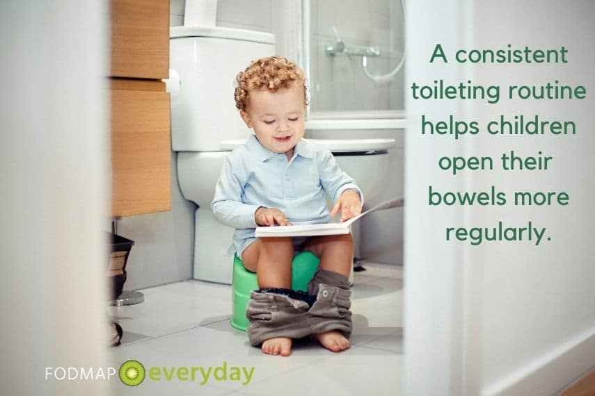 a toddler sitting on the toilet reading a book